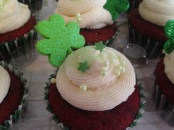 This is a Red Velvet cupcake topped with creamy vanilla frosting and decorated with mint colored candy pearls and holiday green candy decorations.